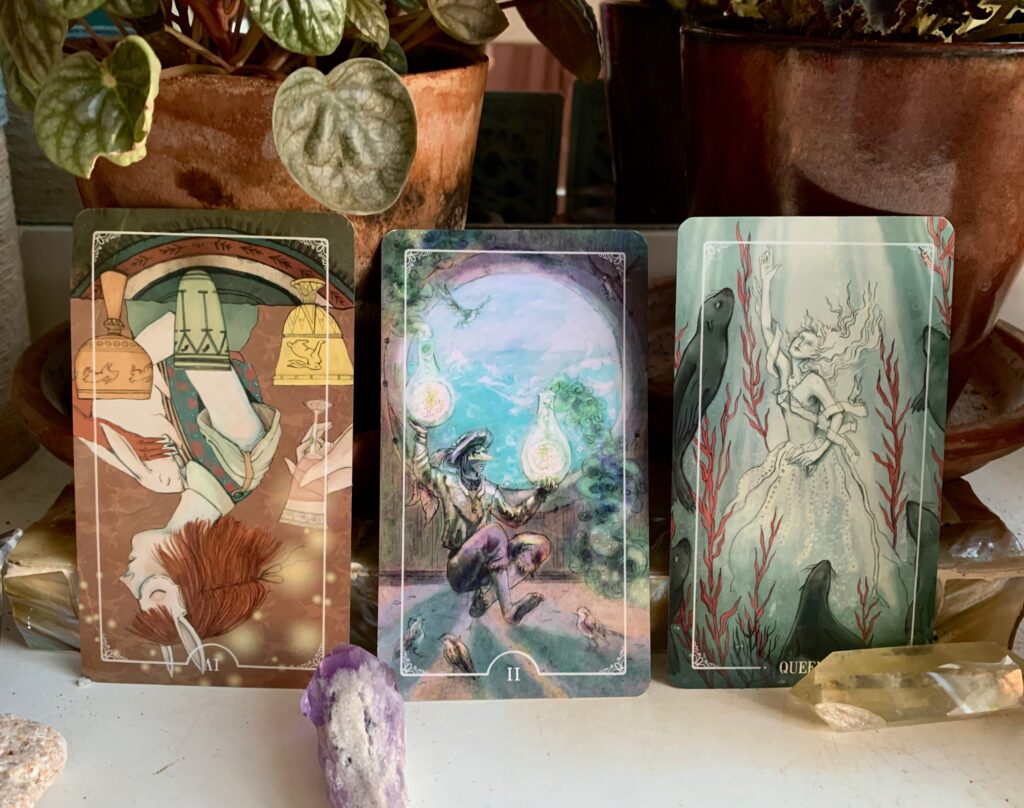 four of cups reversed, two of coins and queen of cups from the ostara tarot deck propped among plants and crystals